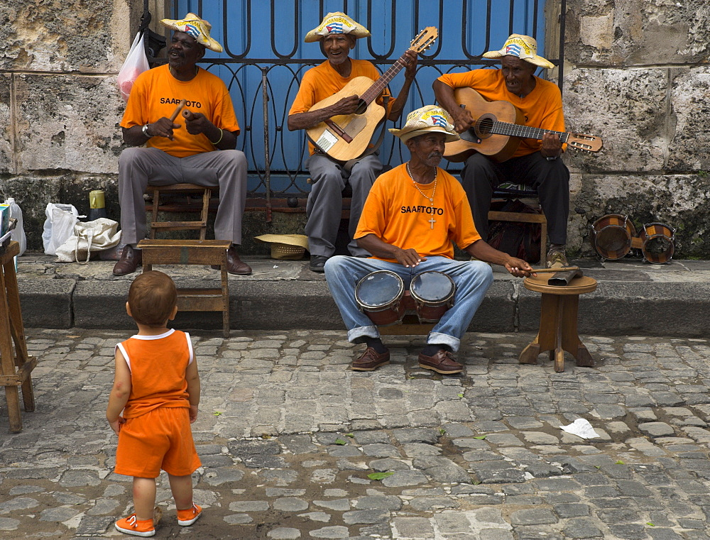 Street band wearing orange shirts playing music on the pavement watched by toddler wearing orange clothes, Habana Vieja (Old Havana), Havana, Cuba, West Indies, Central America