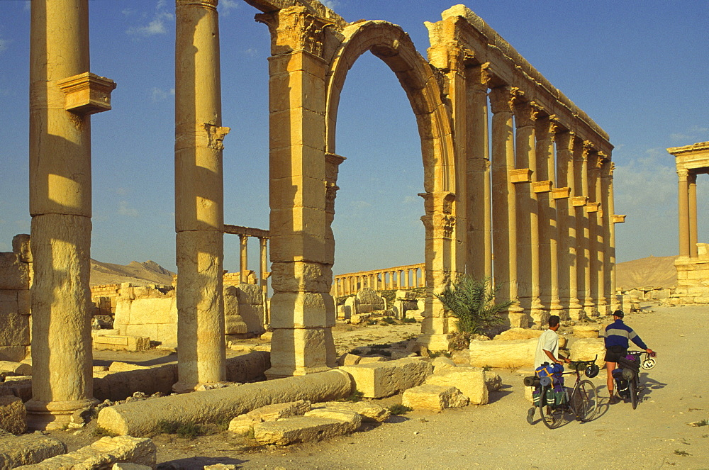 Two cyclists pass the Great Colonnade (Cardo), Palmyra, UNESCO World Heritage Site, Syria, Middle East