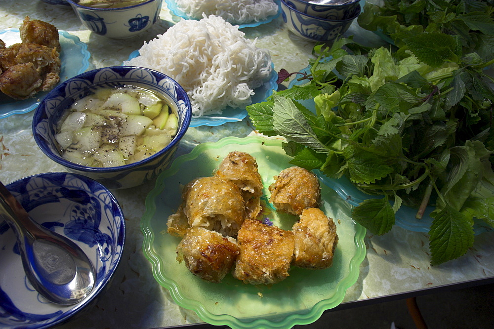 Traditional spring rolls accompanied by vegetable soup, rice noodles and fresh mint and lettuce as side dishes, Nem Ran, Hanoi, Vietnam, Indochina, Southeast Asia, Asia