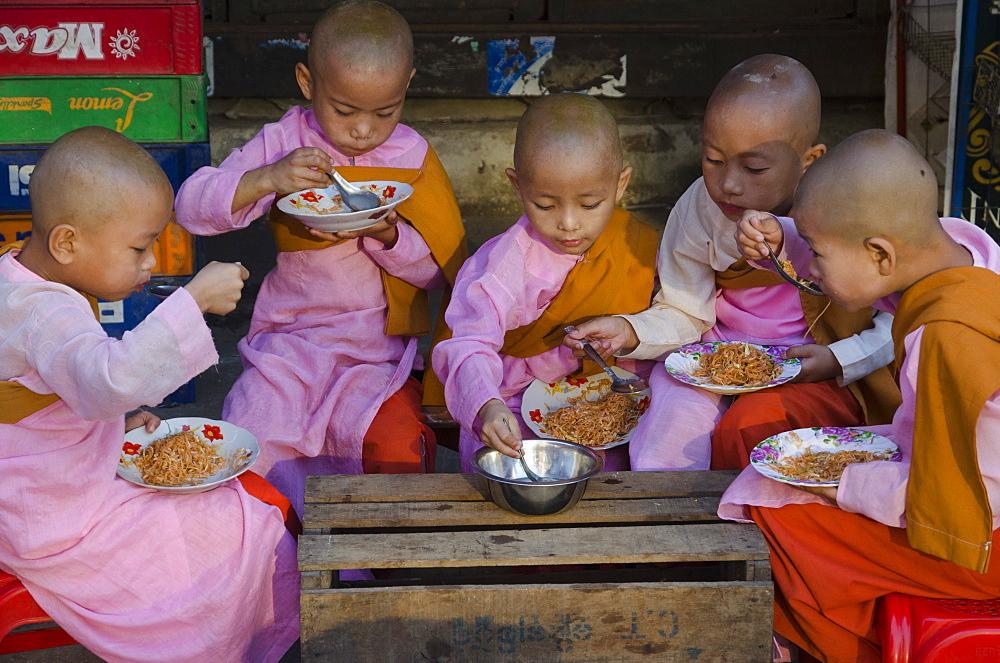 Young novice nuns having their breakfast in the streets of Yangon, Myanmar (Burma), Asia