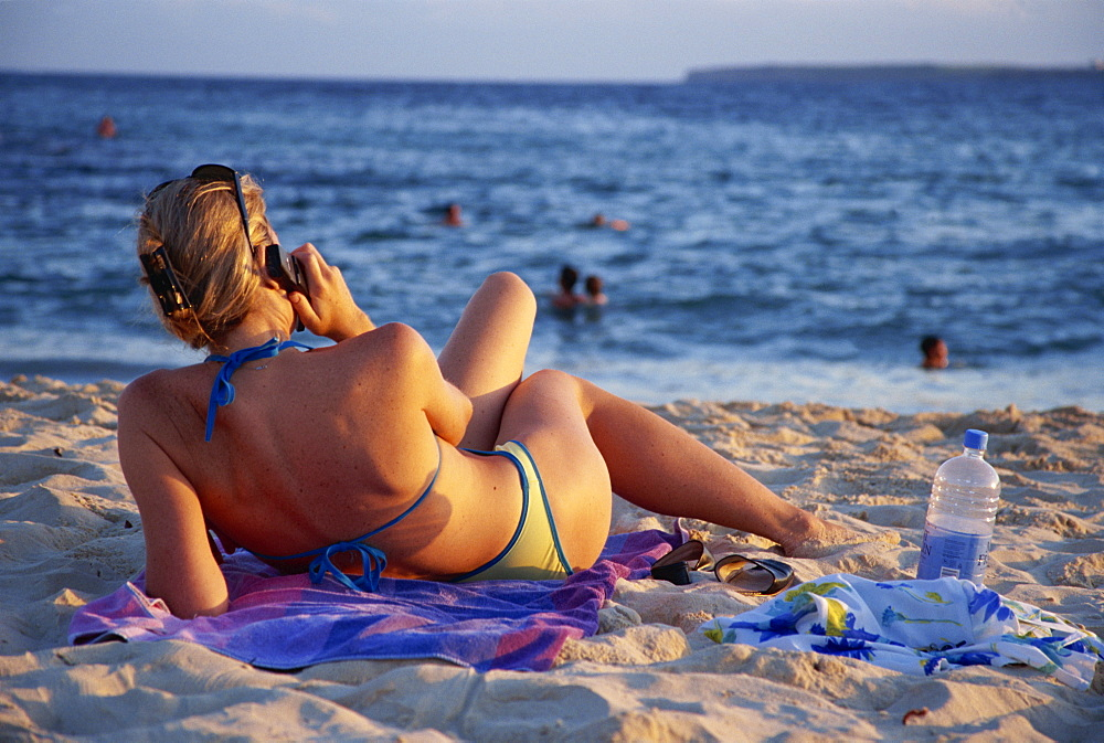 Woman relaxing on Bondi Beach at sundown, using a mobile phone, New South Wales, Australia, Pacific
