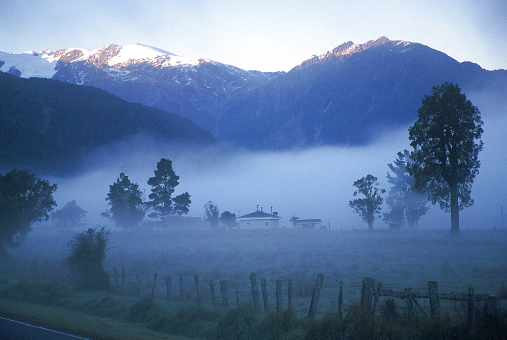 Farm in mist below Fox Glacier, Westland, west coast, South Island, New Zealand, Pacific