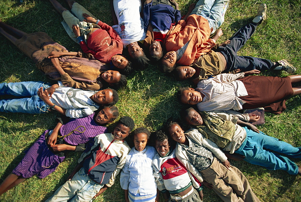 Street kids lying in star formation, Addis Ababa, Ethiopia, Africa