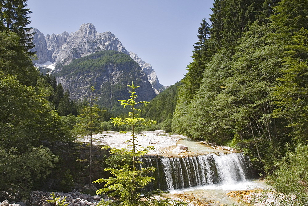 Waterfall over weir on River Velika Pisnca with crystal clear water, Prisank mountain, Triglav National Park, Julian Alps, Kranjska Gora, Dolina, Slovenia, Europe