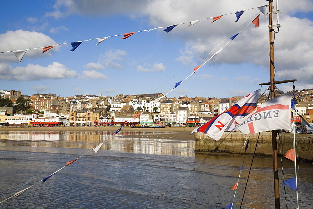 England flag on boat mast in South Bay, with South Sands beach and seafront beyond, Scarborough, North Yorkshire, England, United Kingdom, Europe - 586-1344
