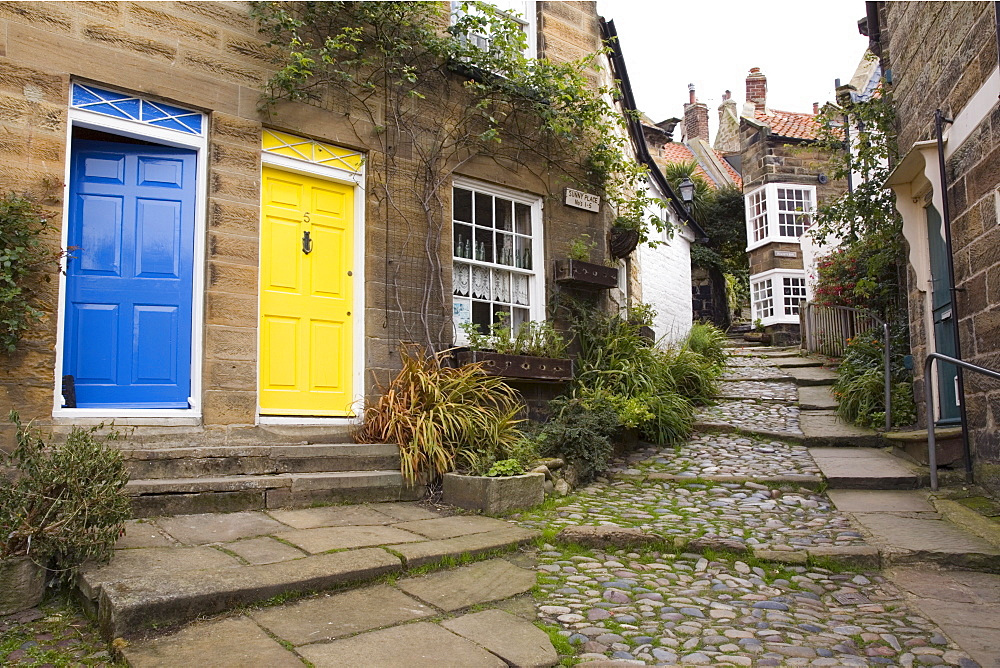 Yellow and blue doors on houses in The Opening, a narrow stepped cobbled alley on steep hill in Old Bay part of the fishing village, Robin Hood's Bay, Yorkshire, England, United Kingdom, Europe - 586-1366