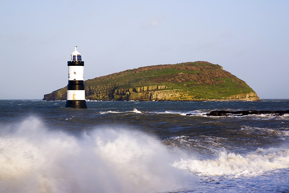 Penmon Point Lighthouse, built in 1838 at the northern entrance to the Menai Strait, and Puffin Island, with rough sea at high tide in winter, Penmon, Anglesey, Wales, United Kingdom, Europe - 586-1386