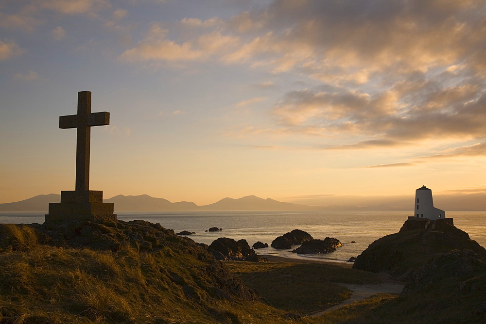 Stone Cross and old lighthouse (Twr Mawr) in silhouette at sunset on rocky tip of Llanddwyn Island National Nature Reserve, Newborough, Anglesey, North Wales, United Kingdom, Europe - 586-1401
