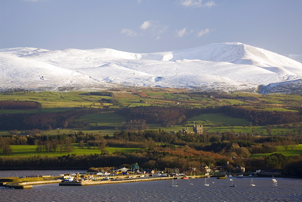 Bangor Port and Penrhyn Castle from across the Menai Strait with snow on mountains of Snowdonia National Park beyond in winter, Menai Bridge, Anglesey, North Wales, United Kingdom, Europe