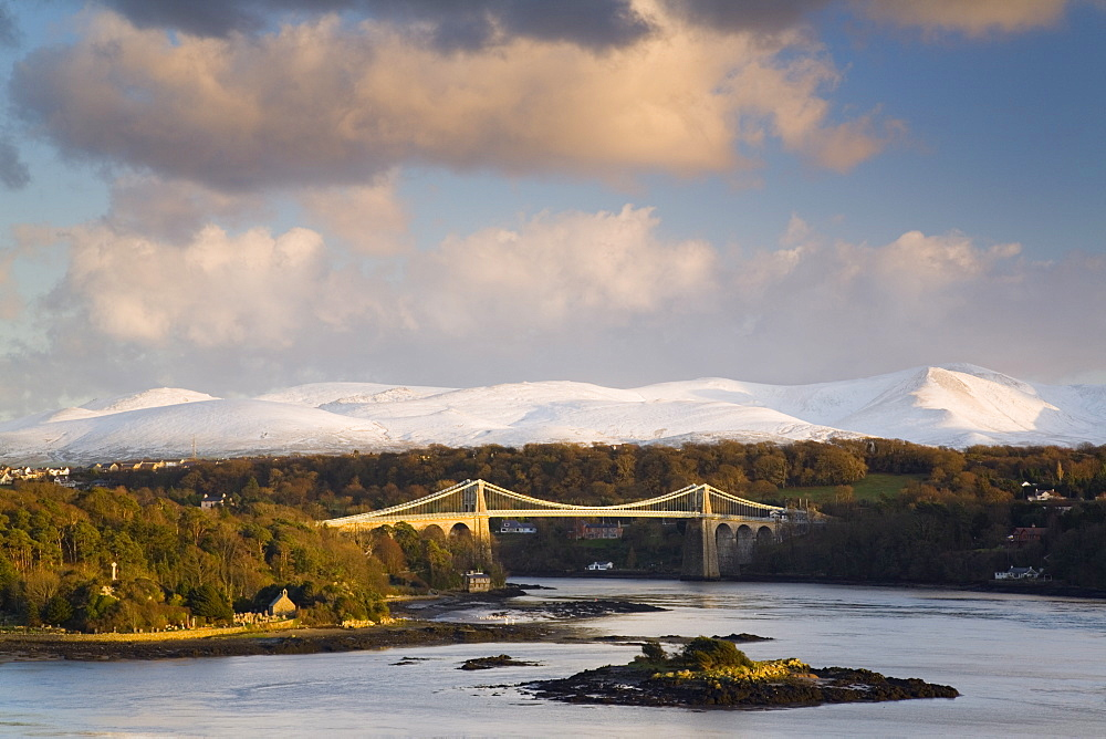 Menai Suspension Bridge built by Thomas Telford in 1826, across the Menai Strait with snow on mountains of Snowdonia in winter evening light, Anglesey, North Wales, United Kingdom, Europe - 586-1403