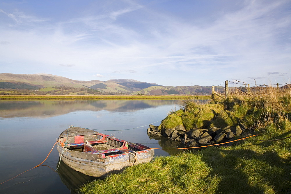 Scenic view with old rowing boat moored on bank in calm water on River Dovey (Afon Dyfi) looking north in low winter sunlight, Glandyfi, Ceredigion, Dyfed, Wales, United Kingdom, Europe - 586-1408