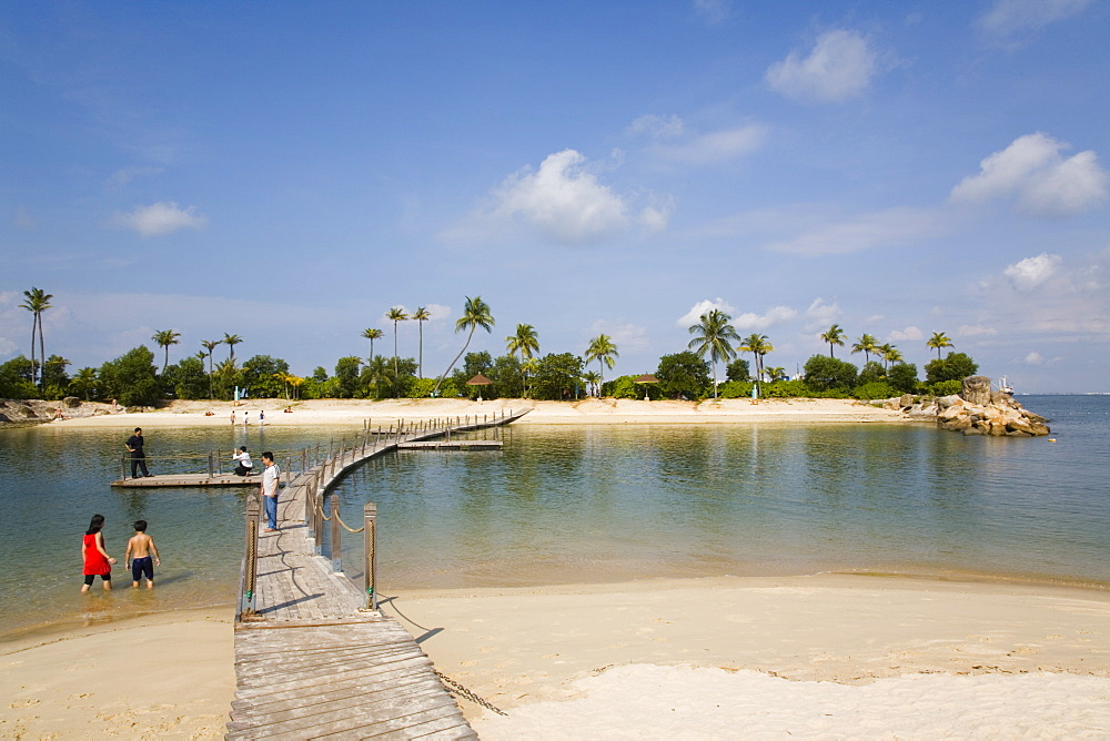 Tropical Siloso beach, sea lagoon and wooden bridge linking small island at western end of southern coast, Sentosa Island, Singapore, Southeast Asia, Asia - 586-1445