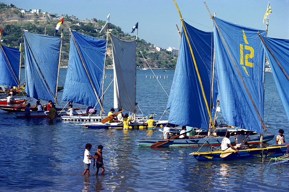 Boats with blue sails line up at the start of a Lakatoi canoe race, Konedobu, Port Moresby, Papua New Guinea, Pacific Islands, Pacific