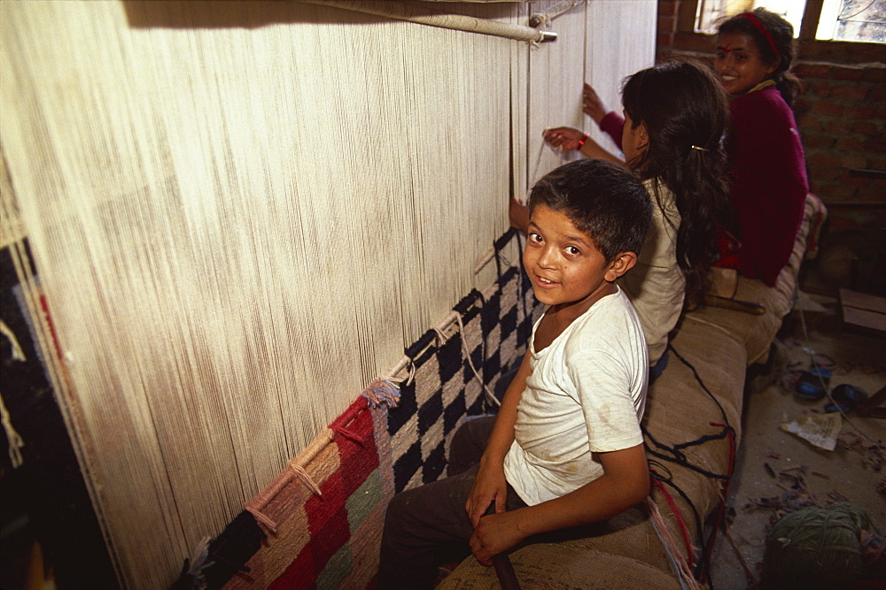 Young children weaving carpets for up to 16 hours a day in carpet factories, Jawlikhel, Kathmandu, Nepal, Asia - 615-184