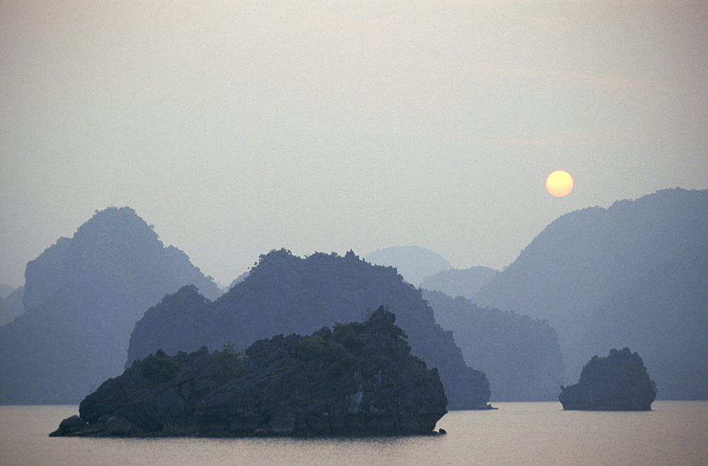 Sunset against limestone grotto islands, Halong Bay, Vietnam, Indochina, Southeast Asia, Asia