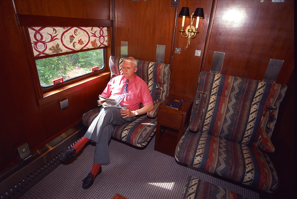 Passenger relaxing in his cabin on the American Orient Express train, travelling in the Southwest U.S., United States of America, North America - 615-397