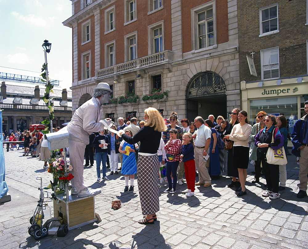 Statue street performer, and group of people watching, Covent Garden, London, England, United Kingdom, Europe