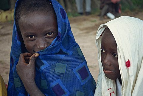 Head and shoulders portrait of two young Gambian children, one looking at the camera, Gambia, West Africa, Africa