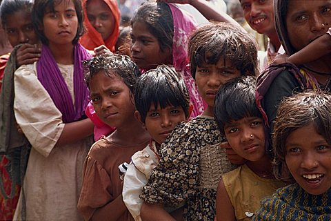 Head and shoulders portrait of a group of Bangladeshi children, looking at the camera, queueing for subsidised rice in Bangladesh, Asia