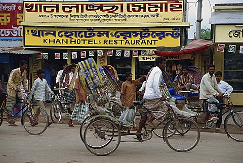 Men riding cycle rickshaws on the street passing the outside of a hotel and restaurant in the city of Dhaka (Dacca), Bangladesh, Asia