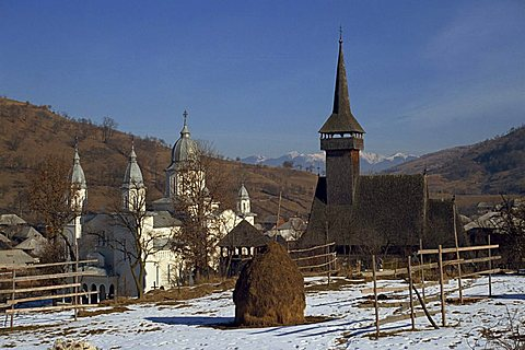 Haystack in snow covered field with two churches in the background at Botita village, Maramures, Romania, Europe