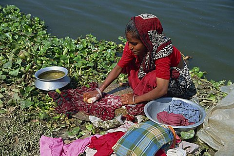 A Bangladeshi woman washing clothes beside the river in Dhaka (Dacca), Bangladesh, Asia