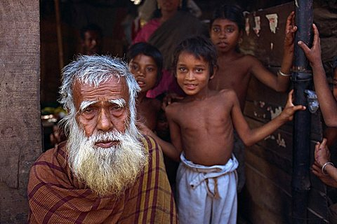 Head and shoulders portrait of an old Bangladeshi (Bengali) man with a white beard, and children beyond, looking at the camera, in the slums of Dhaka (Dacca), Bangladesh, Asia
