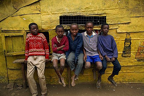 Portrait of a group of five boys, slum children, sitting on a bench outdoors, looking at the camera, Kariobangi, Nairobi, Kenya, East Africa, Africa
