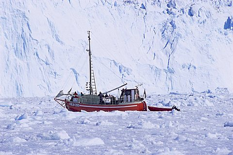 Red wooden boat crossing the ice in front of the Eqi Glacier, near Ilulissat, Greenland, Polar Regions