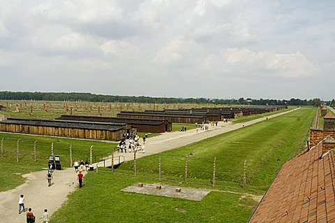 Wooden sheds, formerly stables for horses, that each held 500 prisoners, many now demolished, but chimneys still stand in the background, Auschwitz second concentration camp at Birkenau, UNESCO World Heritage Site, near Krakow (Cracow), Poland, Europe