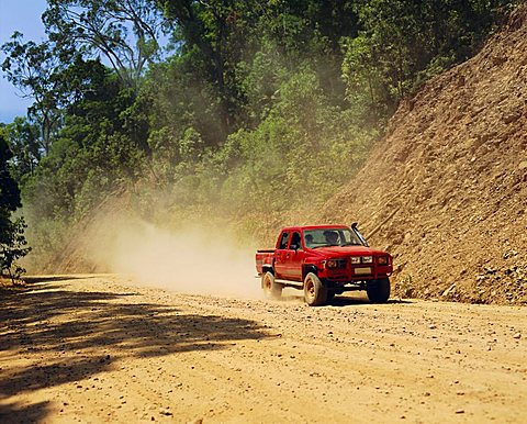 A red 4x4 pick-up on the dusty Bloomfield Track, Cape Tribulation National Park, Queensland, Australia