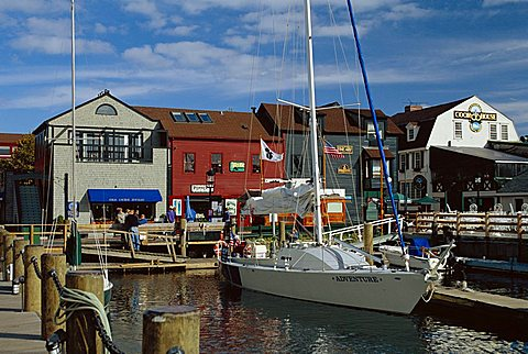 Moored yacht and wooden buildings on the waterfront at Bannister and Bowens Wharves, Newport, Rhode Island, New England, USA