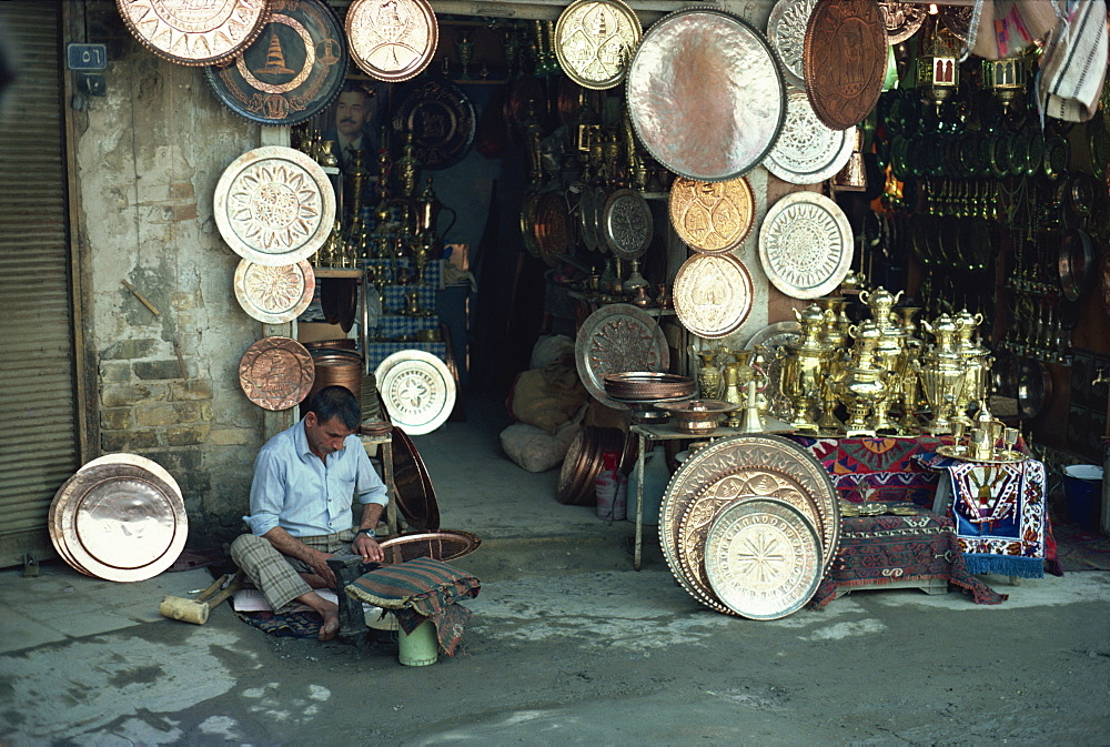 Man working on copper plate outside a copper souk, Baghdad, Iraq, Middle East