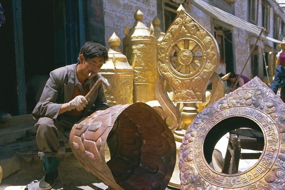 Metalsmith making temple ornaments, Lhasa, Tibet, China, Asia