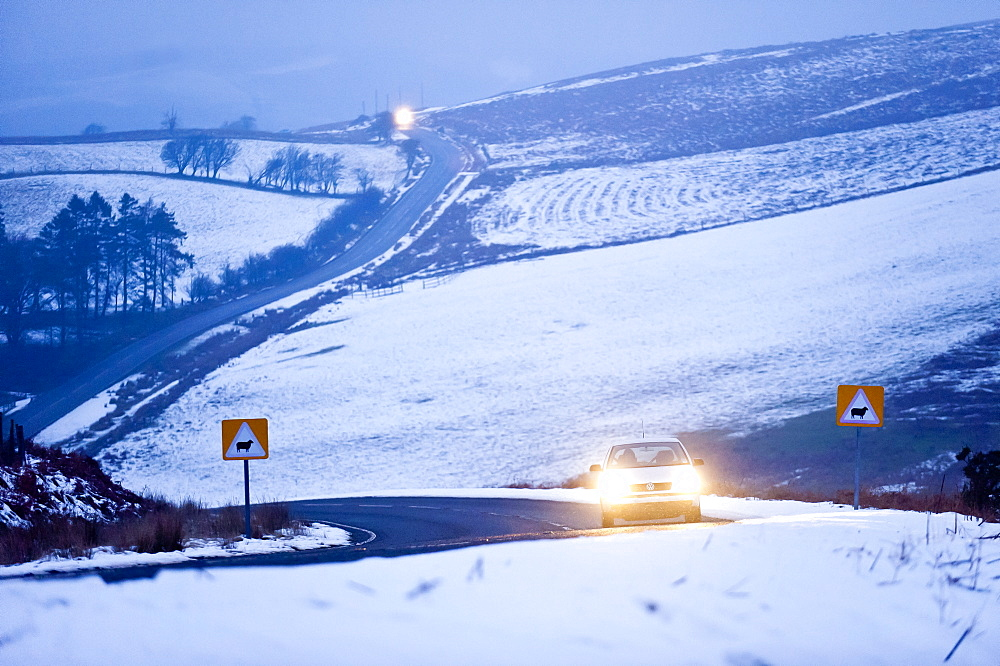 A motorist drives through a wintry landscape on the B4520, Brecon Road, on the Mynydd Epynt moorland, Powys, Wales, United Kingdom, Europe