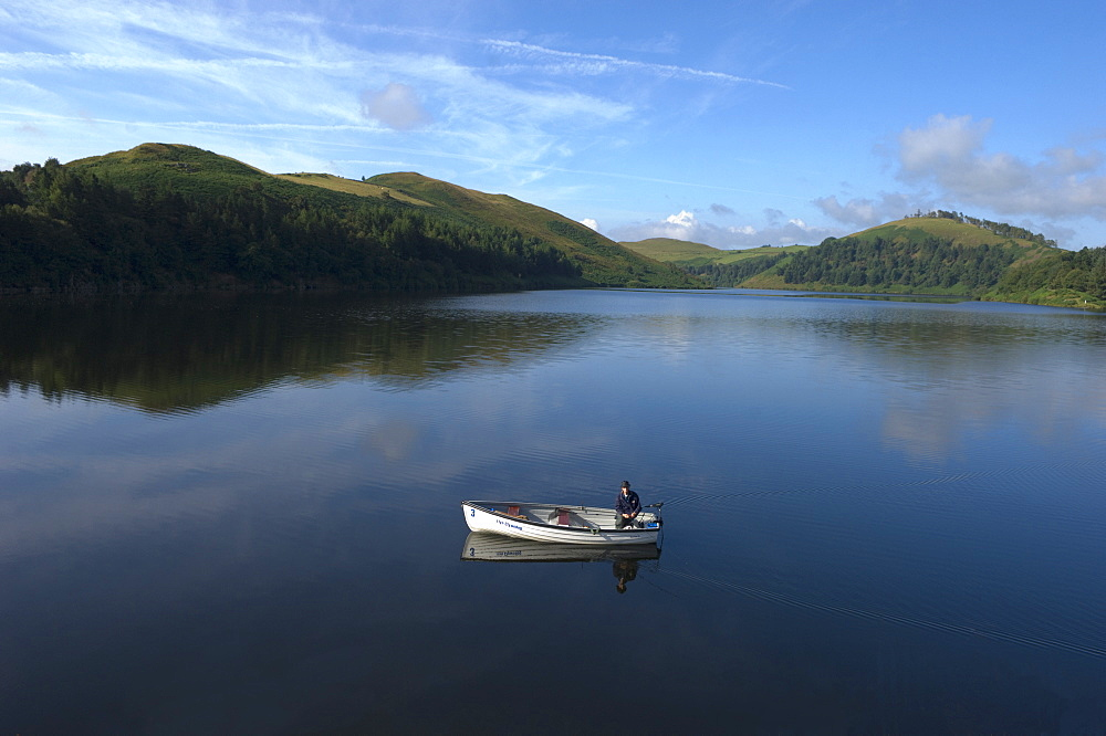 A man fishing from a boat at Llyn (Lake) Clywedog, Llanidloes, Powys, Wales, United Kingdom, Europe