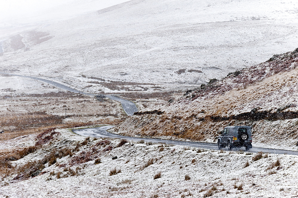 A four wheel drive vehicle negotiates a road through a wintry landscape in the Elan Valley area in Powys, Wales, United Kingdom, Europe - 663-840