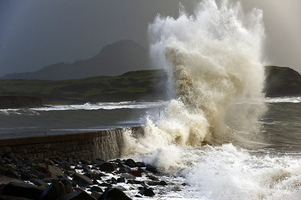 Huge waves crash against a stone jetty at Criccieth, Gwynedd, Wales, United Kingdom, Europe