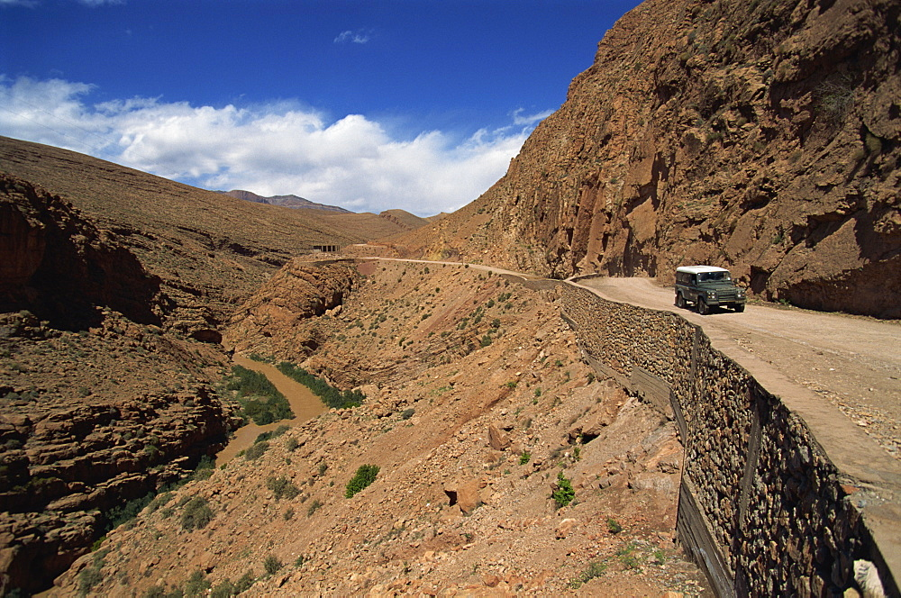 Four-wheel drive vehicle on a road through the Atlas Mountains, in the arid Dades Valley, Morocco, North Africa, Africa