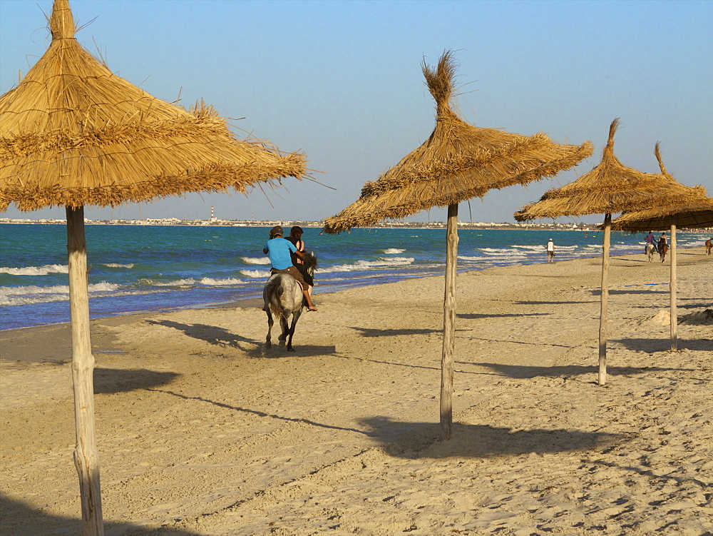 Tourists riding horses on the beach, with palm sunshades, at sunset, Djerba, Tunisia, North Africa, Africa