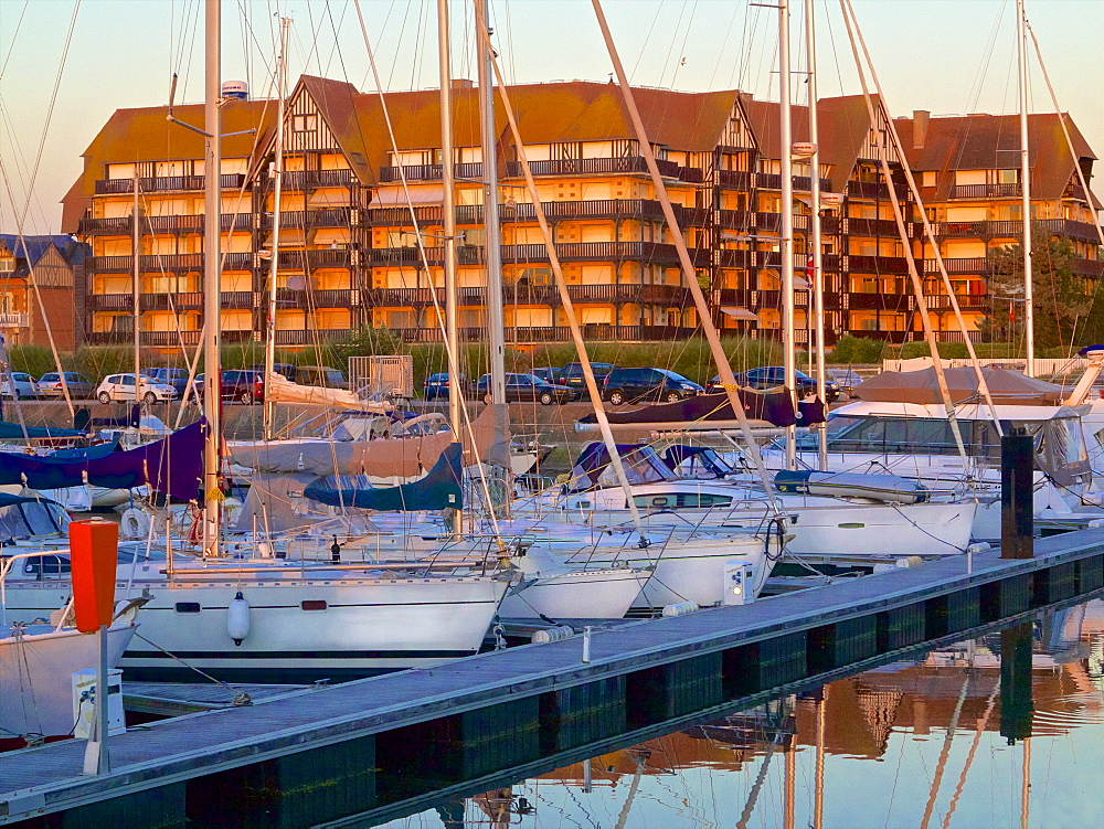 Floating quay and pleasure boats, with contemporary flats in Norman style in the background, at sunset, Port Deauville, Deauville, Calvados, Normandy, France, Europe