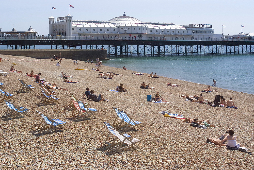 Deck chairs and sunbathers on the pebble beach in view of Brighton Pier, Brighton, Sussex, England, United Kingdom, Europe