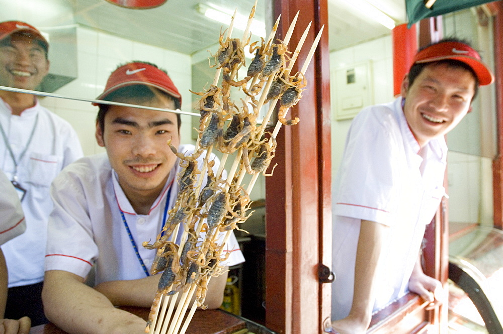 Eating a snack of skewers of scorpion at a hutong near Wang Fu Jing road, where grasshopper, sea horse, snakes, larva and starfish also served, Beijing, China, Asia