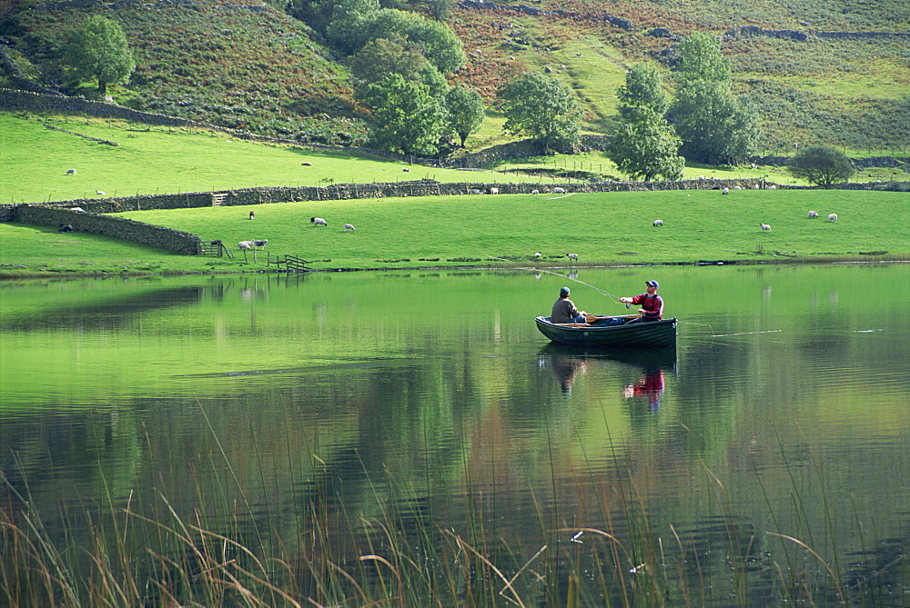 Tranquil scene of two men in a boat on a lake, fly fishing, Watendlath Tarn, Lake District National Park, Cumbria, England, United Kingdom, Europe