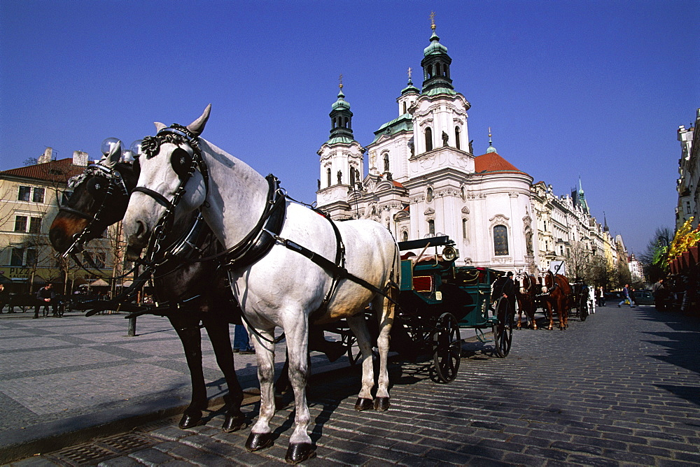 Horse and carriage and church of St. Nicholas, Old Town Square, Prague, Czech Republic, Europe