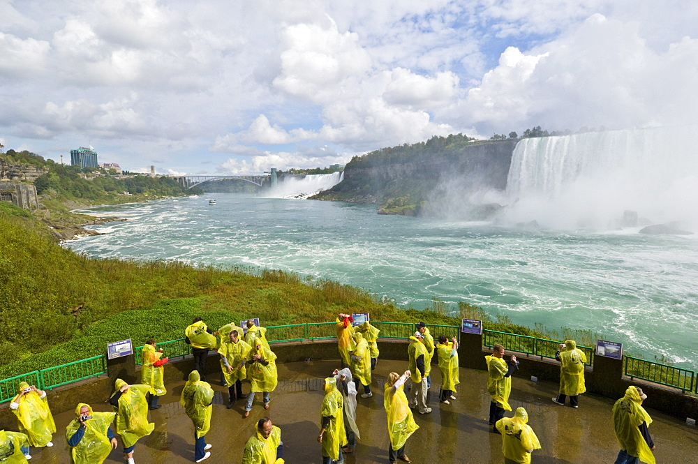 Many tourists in yellow raincoats in the spray of the Horseshoe Falls waterfall whilst on the Journey under the Falls tour, Niagara Falls, Ontario, Canada, North America