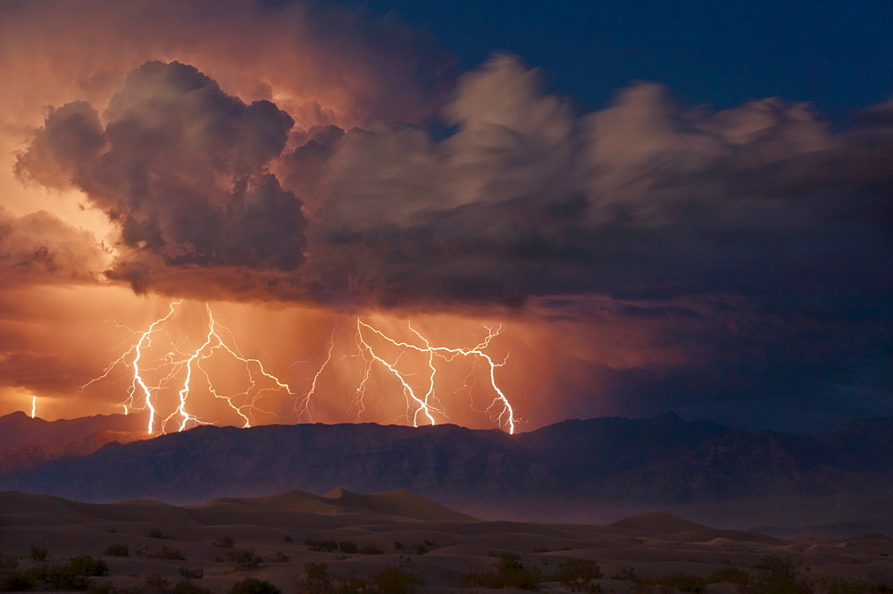 Electrical storm with forked lightning over the Grapevine mountains of the Amargosa Range, Mesquite Flats Sand dunes in the valley, Stovepipe Wells, Death Valley National Park, California, United States of America, North America - 698-2690