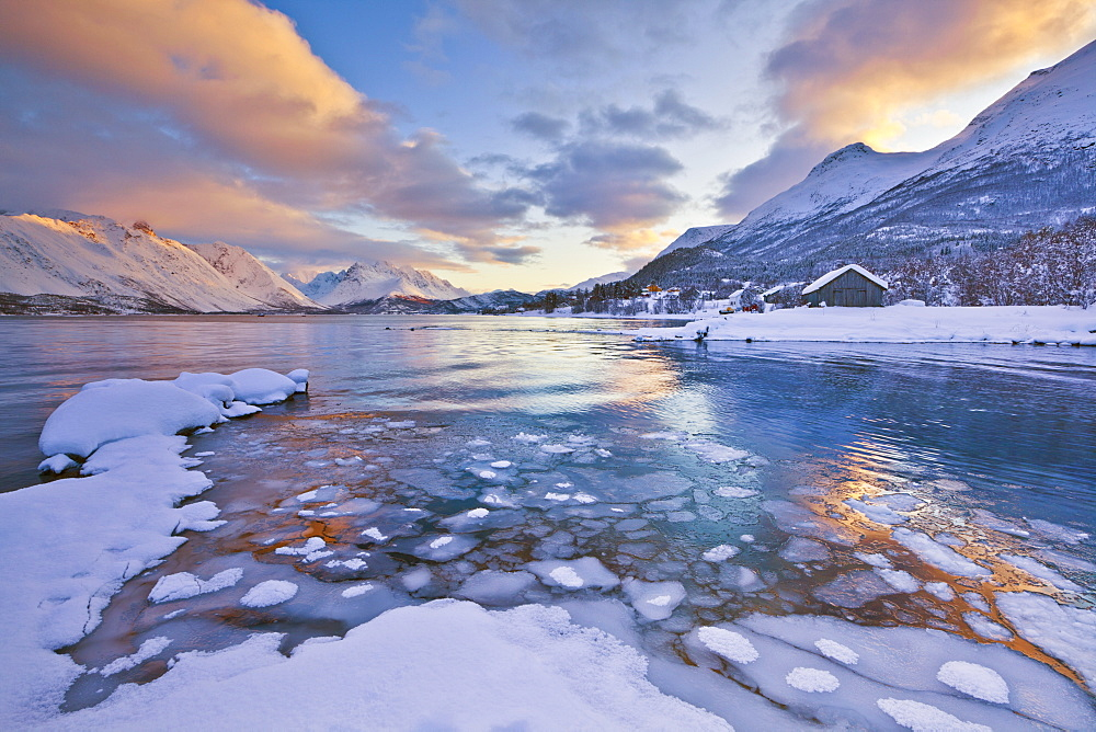 Looking across the frozen sea of Ullsfjord from Sjursnes, towards the Southern Lyngen Alps, at sunset, Troms, Norway, Scandinavia, Europe