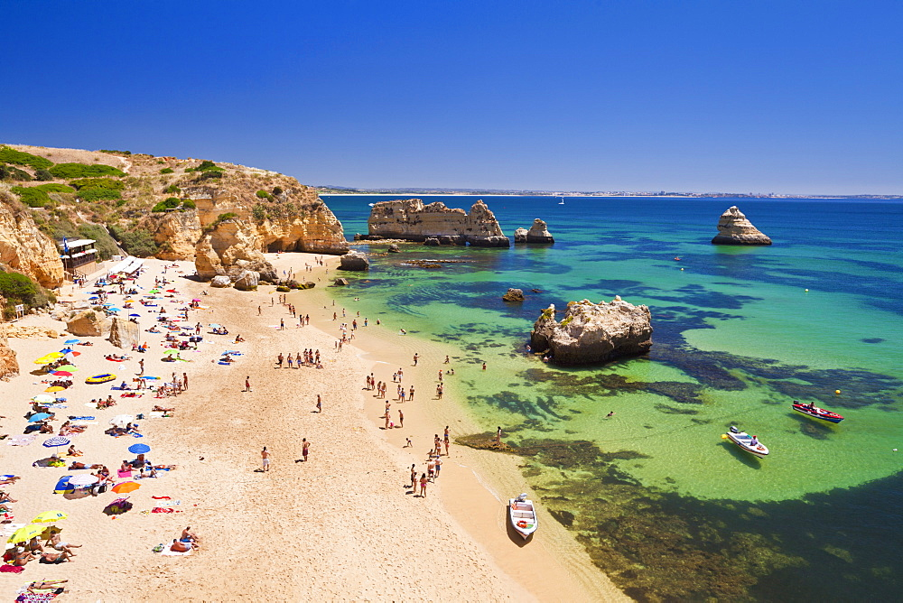 Holidaymakers sunbathing on Praia da Dona Ana, sandy beach near the resort of Lagos, Algarve, Portugal, Europe