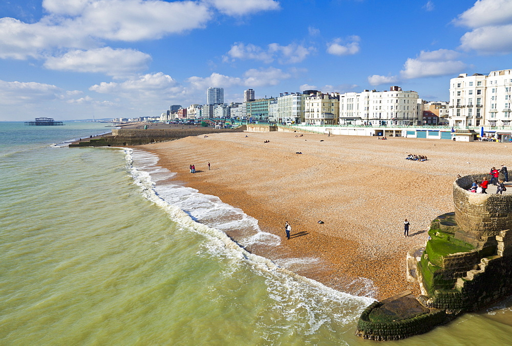 The seafront with people on the beach at Brighton Beach, East Sussex, England, United Kingdom, Europe